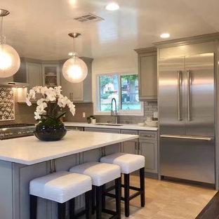 Mittelgroße Klassische Wohnküche in U-Form mit Unterbauwaschbecken, Schrankfronten im Shaker-Stil, grauen Schränken, Speckstein-Arbeitsplatte, Küchenrückwand in Grau, Rückwand aus Porzellanfliesen, Küchengeräten aus Edelstahl, Travertin und Kücheninsel in Los Angeles