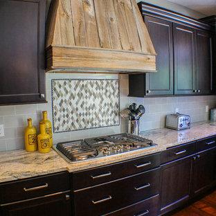 クリーブランドの中サイズのトランジショナルスタイルのおしゃれなキッチン (シェーカースタイル扉のキャビネット、濃色木目調キャビネット、御影石カウンター、グレーのキッチンパネル、セラミックタイルのキッチンパネル、シルバーの調理設備の、濃色無垢フローリング、赤い床) の写真