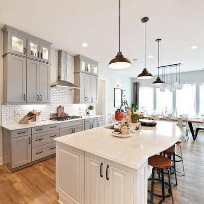Urban light wood floor and beige floor kitchen photo in Charlotte with gray cabinets, quartz countertops, white backsplash, subway tile backsplash, stainless steel appliances, an island and white countertops