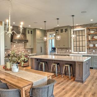 Inredning av ett klassiskt mellanstort vit vitt kök, med en rustik diskho, skåp i shakerstil, stänkskydd i tegel, rostfria vitvaror, en köksö, grå skåp, bänkskiva i kvarts, rött stänkskydd, ljust trägolv och beiget golv