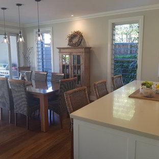 Свежая идея для дизайна: маленькая параллельная кухня-гостиная в современном стиле с накладной раковиной, фасадами в стиле шейкер, белыми фасадами, мраморной столешницей, белым фартуком, фартуком из стекла, белой техникой, полом из бамбука, островом, коричневым полом и бежевой столешницей - отличное фото интерьера