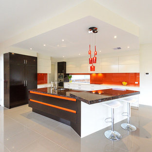 Large contemporary galley open plan kitchen in Melbourne with a drop-in sink, flat-panel cabinets, white cabinets, granite benchtops, orange splashback, glass tile splashback, stainless steel appliances, porcelain floors, with island and grey floor.