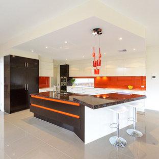 メルボルンの大きいコンテンポラリースタイルのおしゃれなキッチン (ドロップインシンク、フラットパネル扉のキャビネット、白いキャビネット、御影石カウンター、オレンジのキッチンパネル、ガラスタイルのキッチンパネル、シルバーの調理設備の、磁器タイルの床、グレーの床) の写真