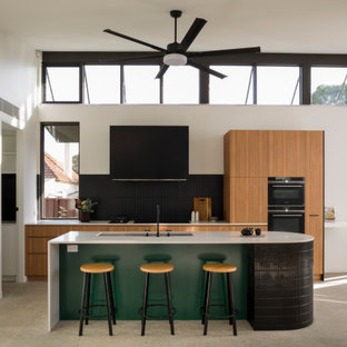 Mid-sized contemporary single-wall open plan kitchen in Sydney with a double-bowl sink, recessed-panel cabinets, light wood cabinets, marble benchtops, black splashback, ceramic splashback, black appliances, concrete floors, with island, grey floor and white benchtop.