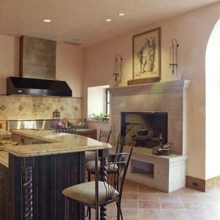 シャーロットの中サイズの地中海スタイルのおしゃれなキッチン (レイズドパネル扉のキャビネット、黒いキャビネット、御影石カウンター、ベージュキッチンパネル、セラミックタイルのキッチンパネル、シルバーの調理設備の、セラミックタイルの床、赤い床) の写真