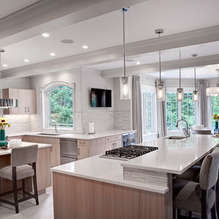 Large transitional kitchen in New York with multiple islands, flat-panel cabinets, beige cabinets, quartz benchtops, grey splashback, stone tile splashback, stainless steel appliances, an undermount sink and porcelain floors.