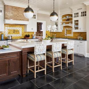 ニューヨークの大きいカントリー風おしゃれなキッチン (エプロンフロントシンク、落し込みパネル扉のキャビネット、グレーのキャビネット、大理石カウンター、黄色いキッチンパネル、セラミックタイルのキッチンパネル、ライムストーンの床、シルバーの調理設備の、黒い床) の写真