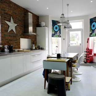 Design ideas for a medium sized eclectic galley kitchen in London with flat-panel cabinets, stainless steel worktops, an island and grey floors.