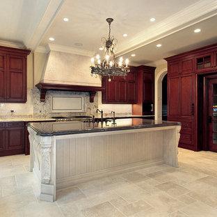 ロサンゼルスの大きい地中海スタイルのおしゃれなキッチン (レイズドパネル扉のキャビネット、赤いキャビネット、白いキッチンパネル、サブウェイタイルのキッチンパネル、パネルと同色の調理設備、トラバーチンの床、ベージュの床) の写真