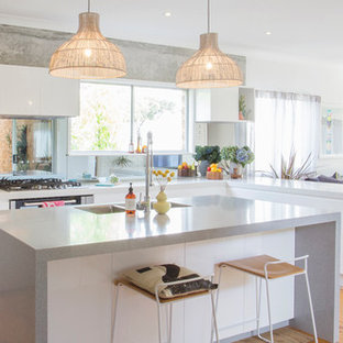 Inspiration for a contemporary l-shaped open plan kitchen in Sydney with a double-bowl sink, flat-panel cabinets, white cabinets, stainless steel appliances, medium hardwood floors, with island, brown floor and grey benchtop.