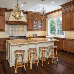 Traditional kitchen appliance - Example of a classic medium tone wood floor kitchen design in Cincinnati with a farmhouse sink, beaded inset cabinets, medium tone wood cabinets, beige backsplash, stainless steel appliances and an island