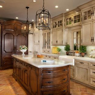 サンディエゴの大きい地中海スタイルのおしゃれなキッチン (エプロンフロントシンク、落し込みパネル扉のキャビネット、ヴィンテージ仕上げキャビネット、大理石カウンター、白いキッチンパネル、石スラブのキッチンパネル、パネルと同色の調理設備、テラコッタタイルの床、赤い床) の写真