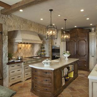 Bild på ett avskilt, stort medelhavsstil u-kök, med integrerade vitvaror, beige skåp, en undermonterad diskho, luckor med infälld panel, marmorbänkskiva, beige stänkskydd, stänkskydd i stenkakel, marmorgolv, en köksö och brunt golv