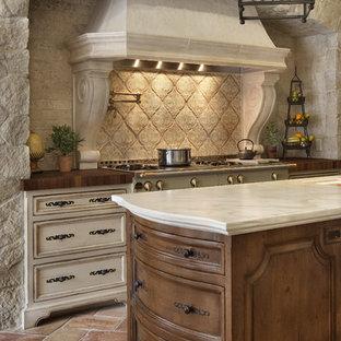 サンディエゴの地中海スタイルのおしゃれなキッチン (テラコッタタイルのキッチンパネル、木材カウンター、落し込みパネル扉のキャビネット、濃色木目調キャビネット、ベージュキッチンパネル) の写真