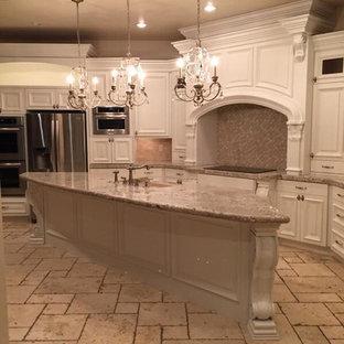 Inspiration för avskilda, mycket stora klassiska l-kök, med en undermonterad diskho, luckor med upphöjd panel, vita skåp, bänkskiva i kalksten, beige stänkskydd, stänkskydd i stenkakel, integrerade vitvaror, tegelgolv och en köksö