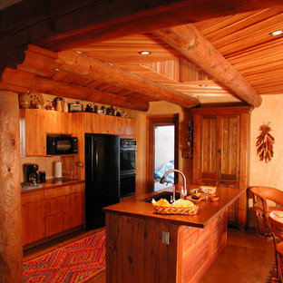 Small southwestern eat-in kitchen remodeling - Example of a small southwest galley concrete floor eat-in kitchen design in Albuquerque with copper countertops, an undermount sink, beaded inset cabinets, light wood cabinets, yellow backsplash, black appliances and an island