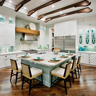 Mid-sized tropical open concept kitchen designs - Example of a mid-sized island style u-shaped medium tone wood floor open concept kitchen design in Miami with a drop-in sink, shaker cabinets, white cabinets, blue backsplash, subway tile backsplash, stainless steel appliances and an island