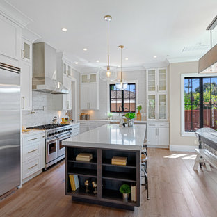 Mid-sized farmhouse eat-in kitchen designs - Eat-in kitchen - mid-sized farmhouse u-shaped medium tone wood floor and brown floor eat-in kitchen idea in San Francisco with a farmhouse sink, white cabinets, quartz countertops, gray backsplash, ceramic backsplash, stainless steel appliances, an island, white countertops and recessed-panel cabinets