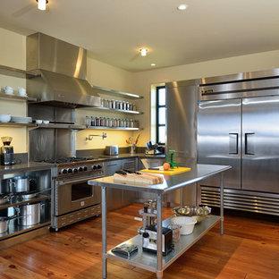 ボイシの広いインダストリアルスタイルのおしゃれなキッチン (アンダーカウンターシンク、フラットパネル扉のキャビネット、ステンレスキャビネット、ステンレスカウンター、メタリックのキッチンパネル、メタルタイルのキッチンパネル、シルバーの調理設備、無垢フローリング) の写真
