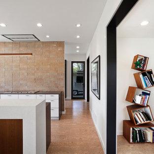 Exempel på ett mellanstort modernt kök, med en undermonterad diskho, släta luckor, vita skåp, bänkskiva i kvarts, orange stänkskydd, stänkskydd i glaskakel, rostfria vitvaror, korkgolv, en köksö och beiget golv