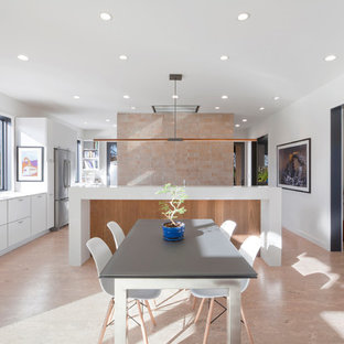 Mid-sized modern l-shaped eat-in kitchen in Indianapolis with an undermount sink, flat-panel cabinets, white cabinets, quartz benchtops, orange splashback, glass tile splashback, stainless steel appliances, cork floors, with island and beige floor.