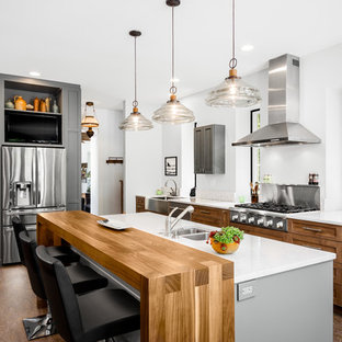 Large contemporary open concept kitchen appliance - Large trendy single-wall cork floor open concept kitchen photo in Philadelphia with a farmhouse sink, shaker cabinets, medium tone wood cabinets, quartz countertops, white backsplash, stone slab backsplash, stainless steel appliances and an island