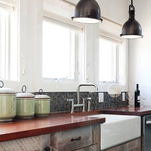 Inspiration for a small contemporary l-shaped open concept kitchen remodel in New York with a farmhouse sink, shaker cabinets, wood countertops, mosaic tile backsplash, an island, distressed cabinets, multicolored backsplash and stainless steel appliances