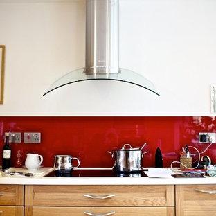 ロンドンの中サイズのカントリー風おしゃれなキッチン (アンダーカウンターシンク、シェーカースタイル扉のキャビネット、ベージュのキャビネット、人工大理石カウンター、赤いキッチンパネル、ガラス板のキッチンパネル、シルバーの調理設備、無垢フローリング、ベージュの床、白いキッチンカウンター) の写真