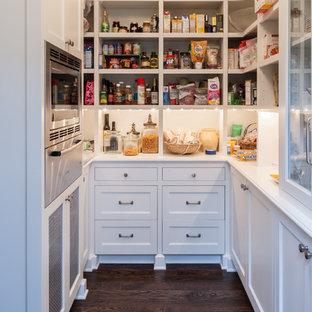 Idées déco pour une arrière-cuisine classique avec un placard avec porte à panneau encastré, des portes de placard blanches, un électroménager en acier inoxydable et un sol en bois foncé.