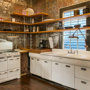 Eclectic kitchen photos - Example of an eclectic l-shaped dark wood floor and brown floor kitchen design in New Orleans with a double-bowl sink, flat-panel cabinets, white cabinets, metallic backsplash, metal backsplash, white appliances and no island
