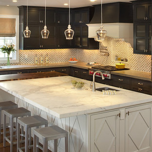 Traditional kitchen pictures - Elegant kitchen photo in San Francisco with stainless steel appliances, recessed-panel cabinets, dark wood cabinets, marble countertops and limestone backsplash