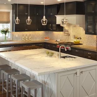 Foto de cocina tradicional con electrodomésticos de acero inoxidable, armarios con paneles empotrados, puertas de armario de madera en tonos medios, encimera de mármol y salpicadero de piedra caliza