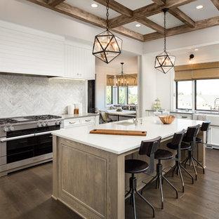 アトランタの大きいカントリー風おしゃれなキッチン (エプロンフロントシンク、落し込みパネル扉のキャビネット、白いキャビネット、人工大理石カウンター、グレーのキッチンパネル、大理石の床、シルバーの調理設備の、濃色無垢フローリング、茶色い床、白いキッチンカウンター) の写真