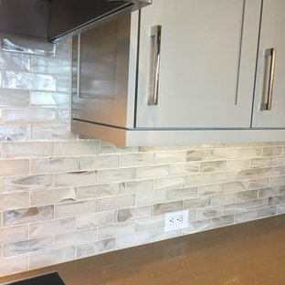 Design ideas for a large industrial l-shaped open plan kitchen in Atlanta with a farmhouse sink, shaker cabinets, grey cabinets, recycled glass benchtops, white splashback, glass tile splashback, stainless steel appliances, with island and beige floor.