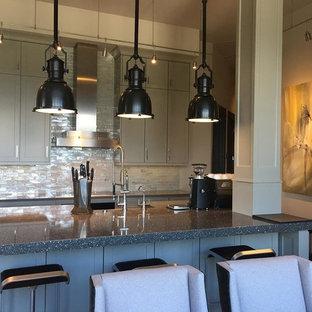 Diseño de cocina en L, urbana, grande, abierta, con fregadero sobremueble, armarios estilo shaker, puertas de armario grises, encimera de vidrio reciclado, salpicadero blanco, salpicadero de azulejos de vidrio, electrodomésticos de acero inoxidable, una isla y suelo beige