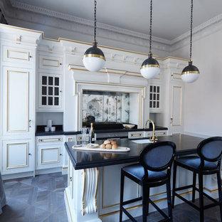 Immagine di una cucina parallela tradizionale di medie dimensioni con lavello sottopiano, paraspruzzi a effetto metallico, paraspruzzi a specchio, isola, pavimento nero, top nero, ante con riquadro incassato, ante bianche, elettrodomestici da incasso e parquet scuro