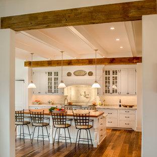 Geräumige Landhaus Wohnküche in L-Form mit profilierten Schrankfronten, weißen Schränken, Küchenrückwand in Weiß, Rückwand aus Steinfliesen, Küchengeräten aus Edelstahl, Marmor-Arbeitsplatte, braunem Holzboden, Kücheninsel, Landhausspüle und braunem Boden in Philadelphia