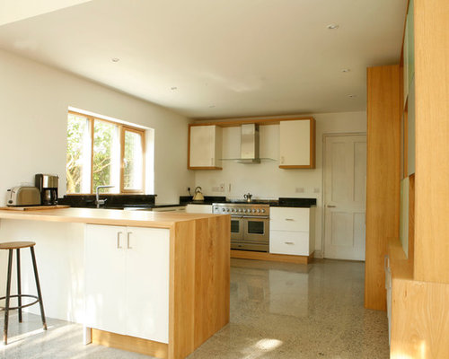 Example Of A Minimalist U Shaped Kitchen Design In Dublin With A Farmhouse  Sink,
