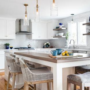 Modelo de cocina comedor en L, costera, con puertas de armario blancas, salpicadero blanco, electrodomésticos de acero inoxidable, suelo de madera en tonos medios, una isla, suelo marrón y encimeras blancas