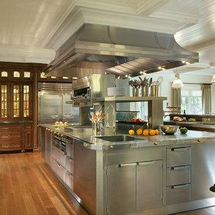 Idéer för mycket stora vintage u-kök, med en enkel diskho, luckor med profilerade fronter, vita skåp, granitbänkskiva, stänkskydd med metallisk yta, stänkskydd i metallkakel, rostfria vitvaror, mellanmörkt trägolv och flera köksöar