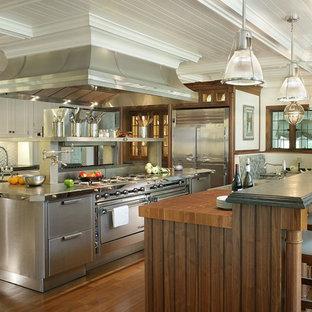 Foto på ett mycket stort vintage kök och matrum, med luckor med profilerade fronter, skåp i rostfritt stål, stänkskydd med metallisk yta, rostfria vitvaror, en nedsänkt diskho, stänkskydd i metallkakel, mellanmörkt trägolv, flera köksöar och bänkskiva i rostfritt stål