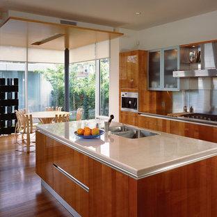 Esempio di una cucina moderna con elettrodomestici in acciaio inossidabile, lavello a doppia vasca, ante marroni, paraspruzzi a effetto metallico e paraspruzzi con piastrelle di metallo