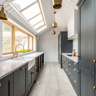This is an example of a classic galley kitchen in Kent with a belfast sink, quartz worktops, white splashback, no island, white worktops, shaker cabinets, black cabinets and grey floors.