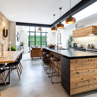 Inspiration for a medium sized industrial kitchen/diner in West Midlands with a submerged sink, flat-panel cabinets, dark wood cabinets, glass sheet splashback, stainless steel appliances, concrete flooring, an island and grey floors.