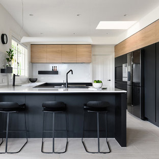 Photo of a contemporary u-shaped separate kitchen in Hobart with a drop-in sink, flat-panel cabinets, black cabinets, white splashback, black appliances, a peninsula, beige floor and white benchtop.
