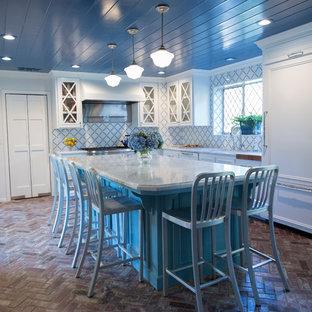 Inredning av ett klassiskt kök, med vita skåp, blått stänkskydd, stänkskydd i keramik, tegelgolv och en köksö
