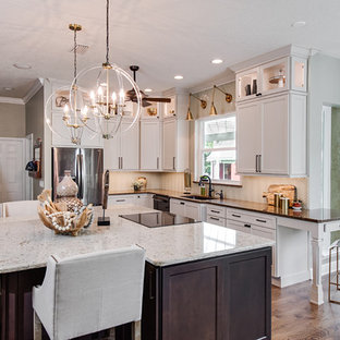 This is an example of a classic l-shaped open plan kitchen in Orlando with a submerged sink, shaker cabinets, white cabinets, beige splashback, an island, quartz worktops, glass tiled splashback, stainless steel appliances, medium hardwood flooring, purple floors and multicoloured worktops.