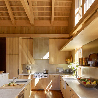 Inspiration for a country l-shaped kitchen in Portland with flat-panel cabinets, light wood cabinets, quartzite benchtops, medium hardwood floors, with island, beige benchtop, a farmhouse sink, beige splashback and stainless steel appliances.