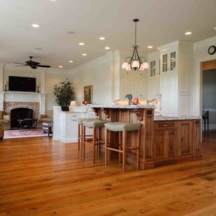 Huge elegant galley medium tone wood floor eat-in kitchen photo in DC Metro with a drop-in sink, raised-panel cabinets, medium tone wood cabinets, marble countertops, white appliances and an island