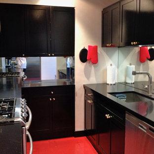 ニューヨークの小さいおしゃれなキッチン (アンダーカウンターシンク、黒いキャビネット、人工大理石カウンター、ミラータイルのキッチンパネル、シルバーの調理設備の、リノリウムの床、アイランドなし、赤い床) の写真